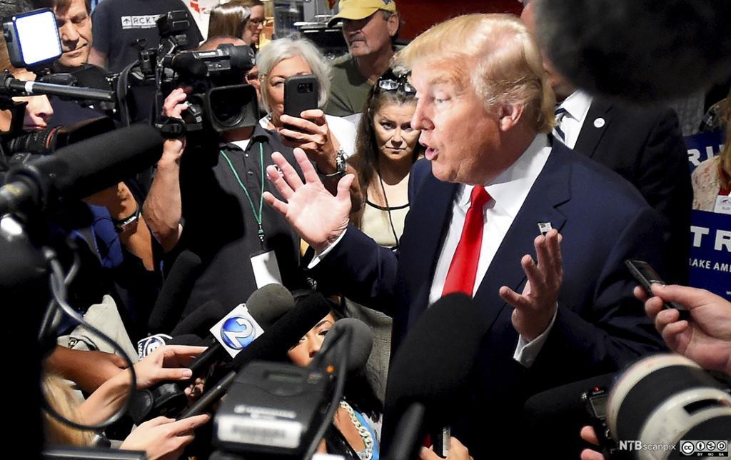 Den republikanske presidentkandidaten Donald Trimp omgitt av mikrofoner og kameraer. Foto.