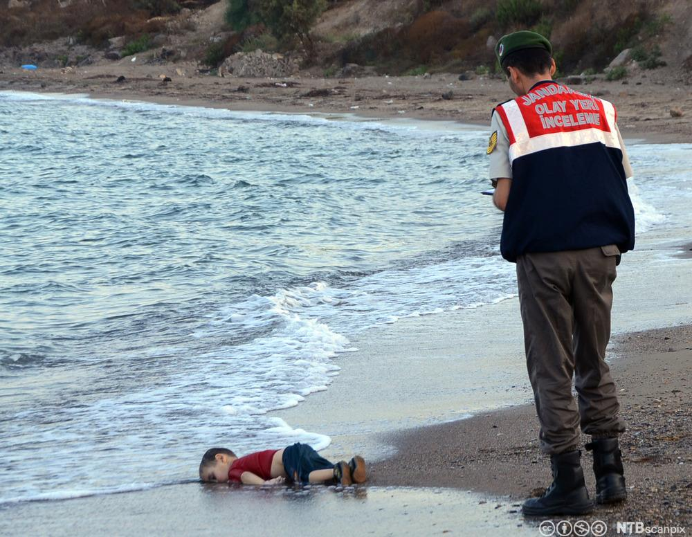 En druknet treåring er skylt på land på en sandstrand, en tyrkisk politimann nærmer seg. Fotografi.
