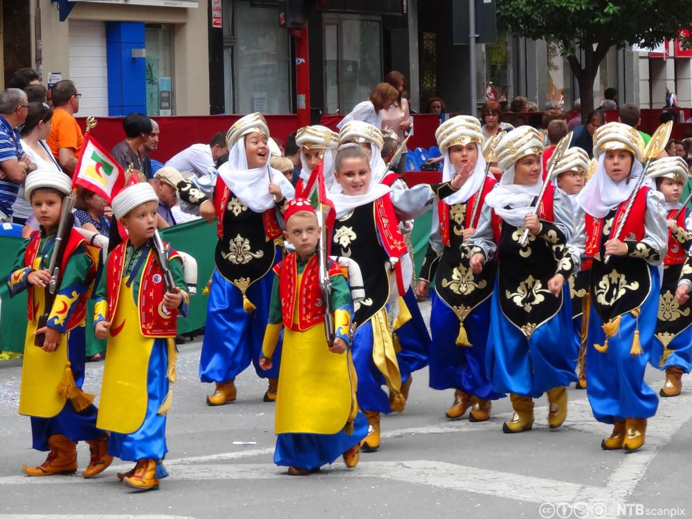 Barn i fargerike mauriske drakter under feiringen av Moros y cristianos, festival som feirer sameksistens mellom maurerne og de kristne. Foto.