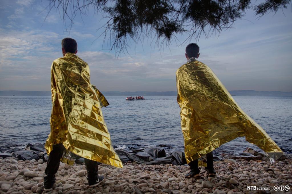 To menn innpakket i folie for å få varme i kroppen ser en ny båtlast med flyktninger i gymmibåt på vei mot land. Foto.