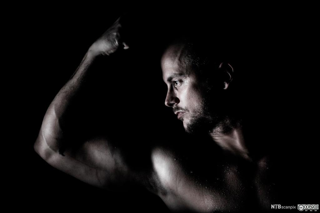 Mann som flekser muskler. Foto.