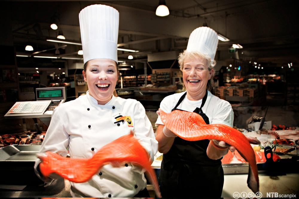 To glade damer som selger fisk. Foto.