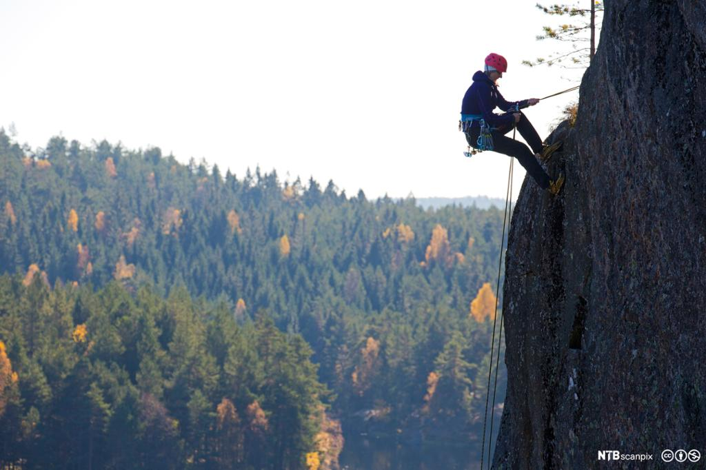 Klatrer opp på fjelltopp. Foto.