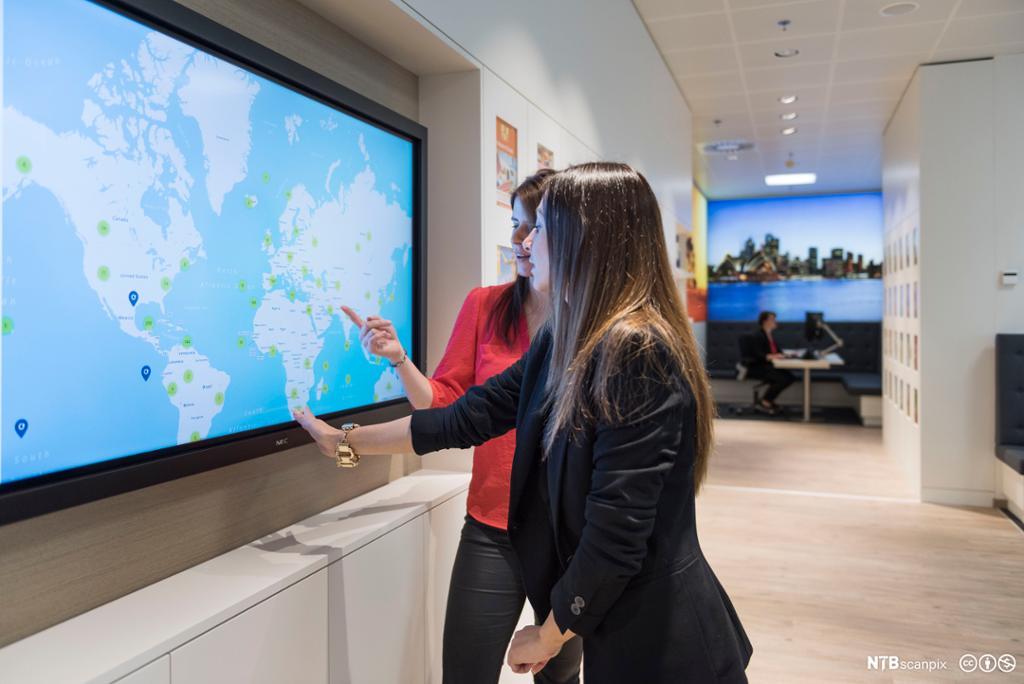 Kundebehandler og kunde ser på et kart med mulige reisemål. Foto.
