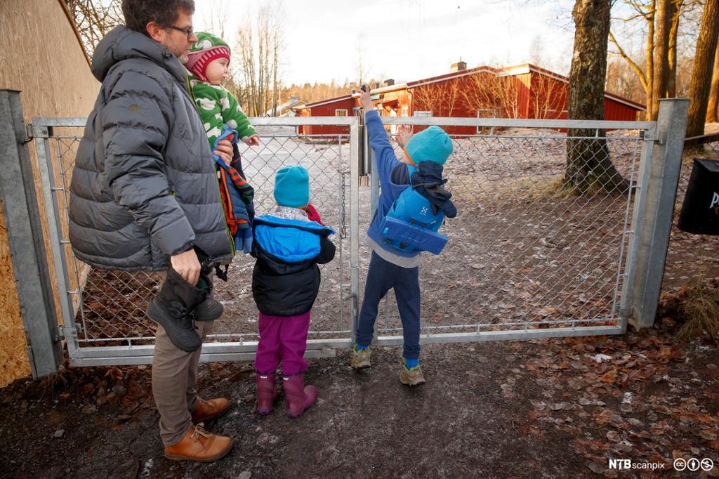 Far og barn ved barnehage. Foto.