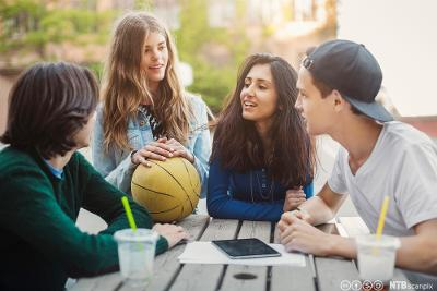 Fire ungdommer som sitter rundt et bord i skolegården og prater. Foto.