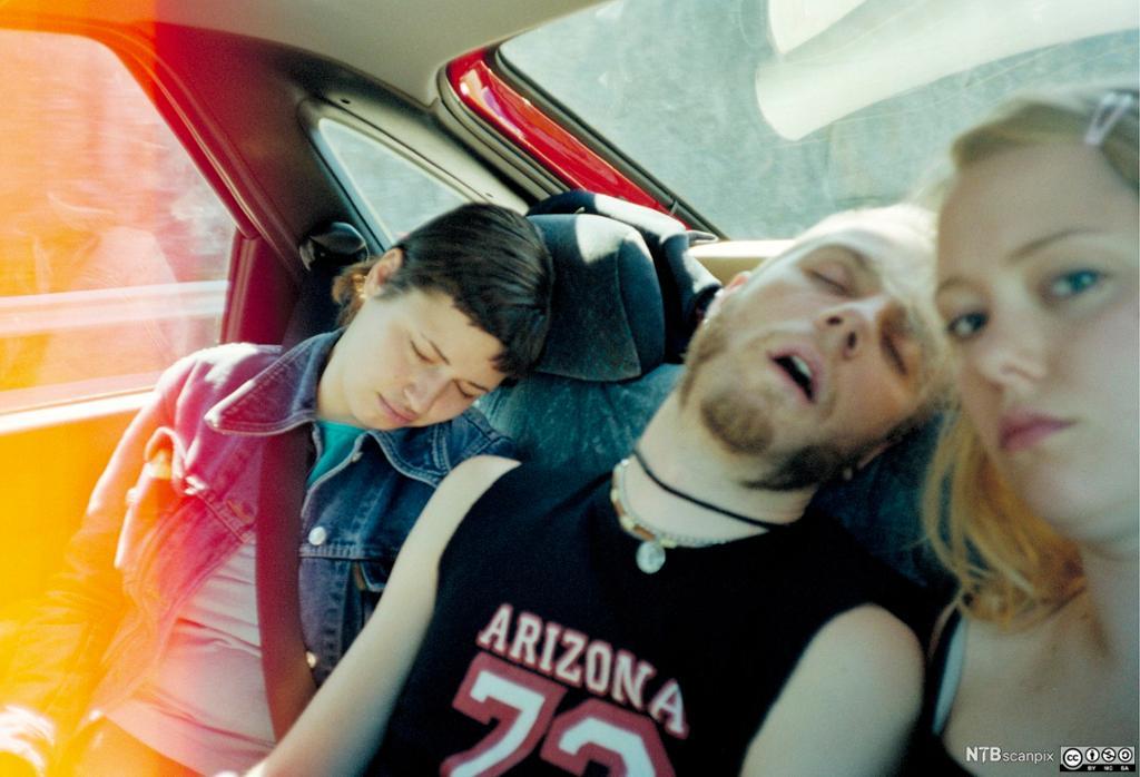 Tre ungdommer i baksete på en bil. Foto.