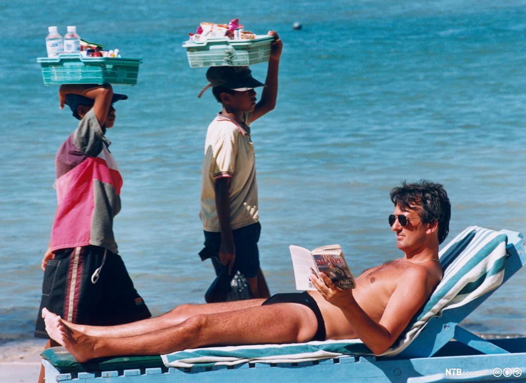Turist på solseng slapper av på stranda. Foto.