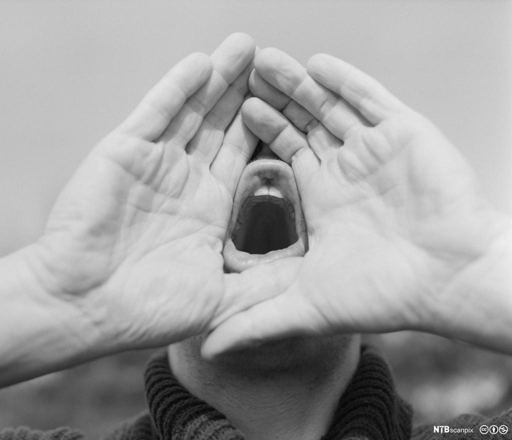 Person som bruker hendene som ropert. Foto.