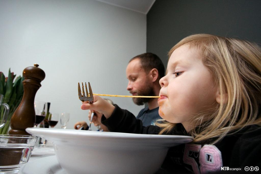 Liten jente spiser spagetti. Foto.