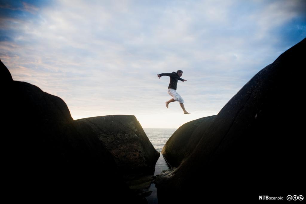 Ung mann som hopper over bergsprekk. Foto.