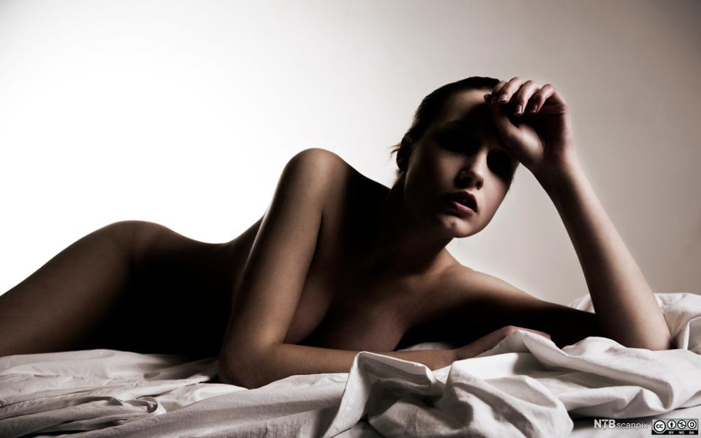 Naken kvinne mellom lakener. Foto.