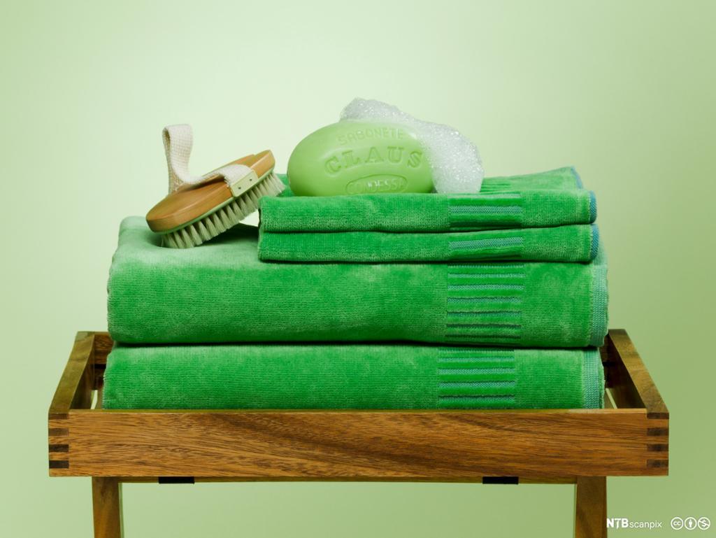 Grønt såpestykke ligger oppå stabel med grønne håndklær. Foto.