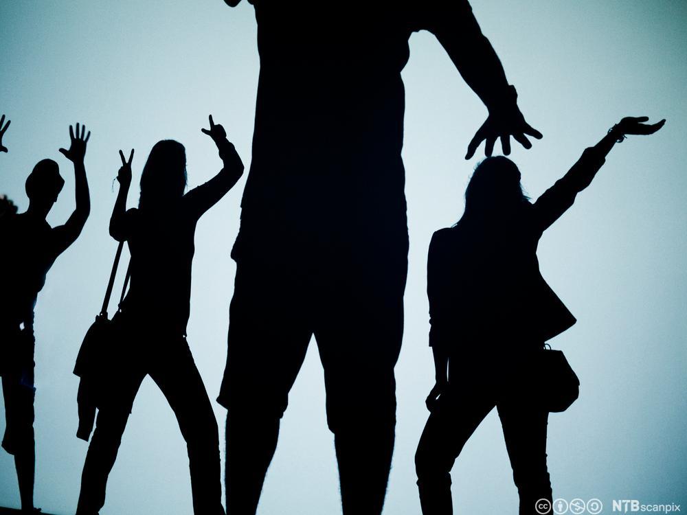 Silhuett av fire dansende ungdommer. Foto.