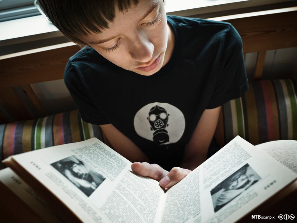 Gutt som leser bok. Foto.