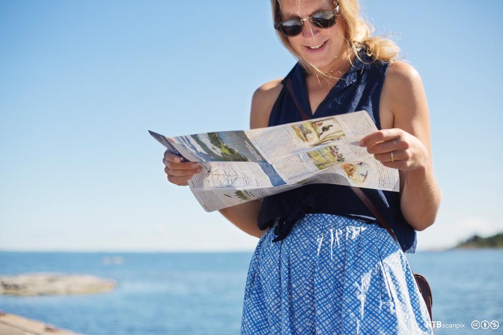 En glad, ung kvinnelig turist i kjole og solbriller står ved havet og ser på et kart. Foto.