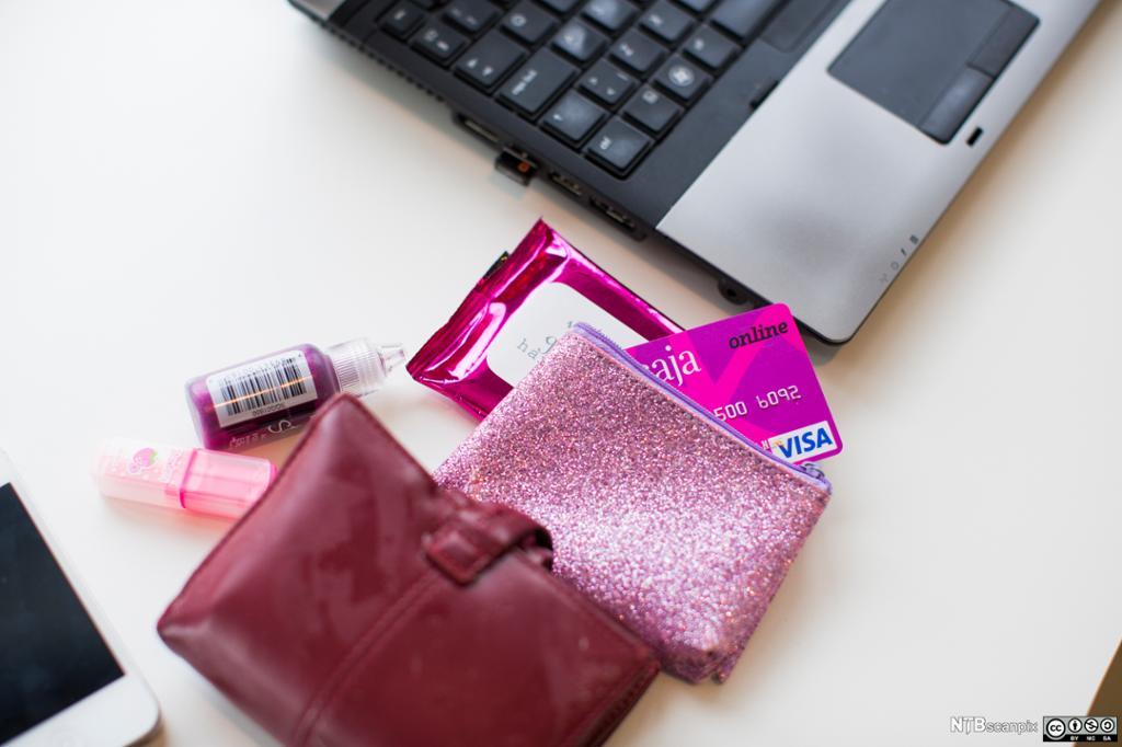 Lommebok med kredittkort ved siden av en pc. Foto.