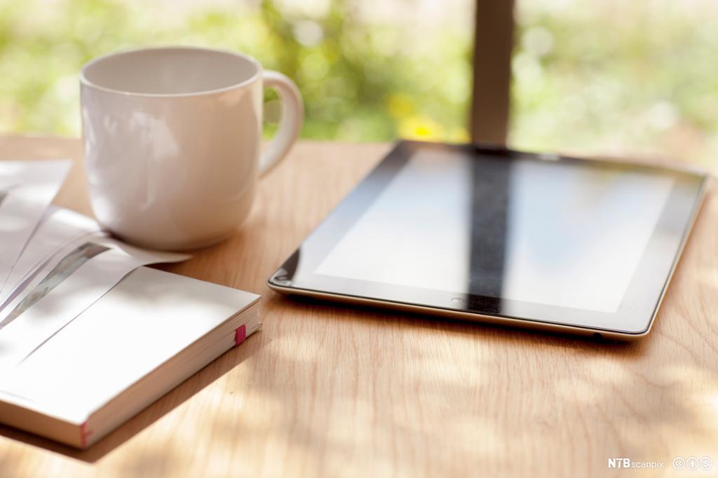 Bord med kaffekopp, ipad og notatbok. Foto.