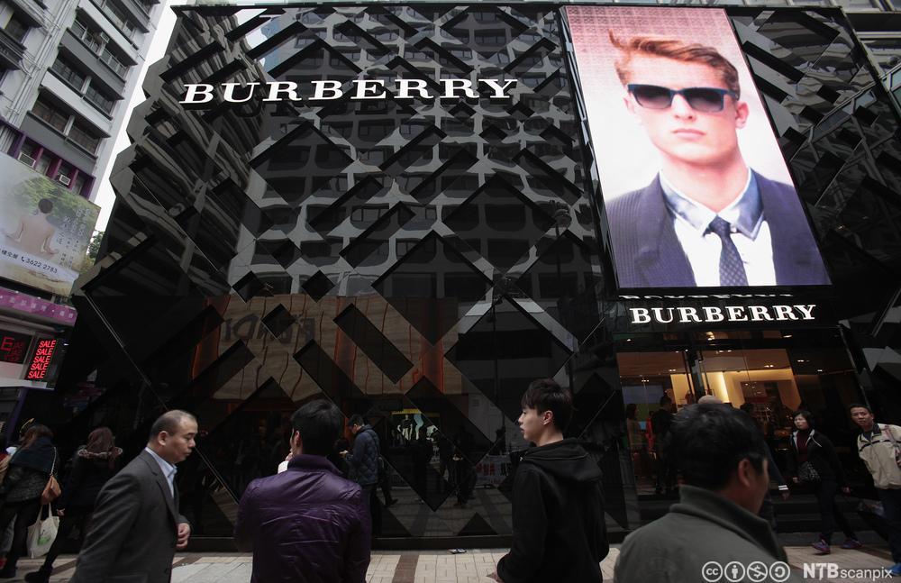 Folk passerer utenfor en Burberry butikk i Hong Kong. Foto.