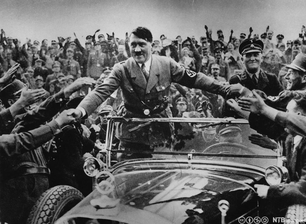 Hitler stående i bil hilser på tilhengere langs under den 5. partikongressen i Nürnberg i 1933. Foto.