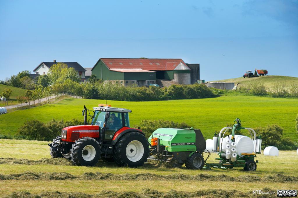 Traktor med rundballepresse. Foto.