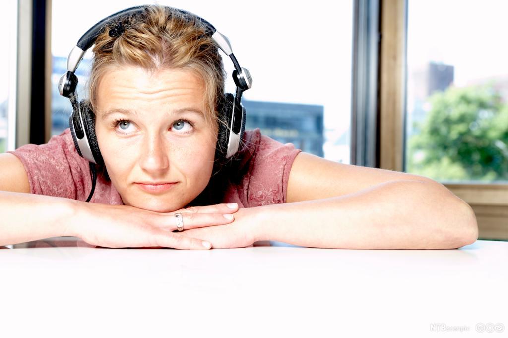 Jente med hodetelefoner. Foto.