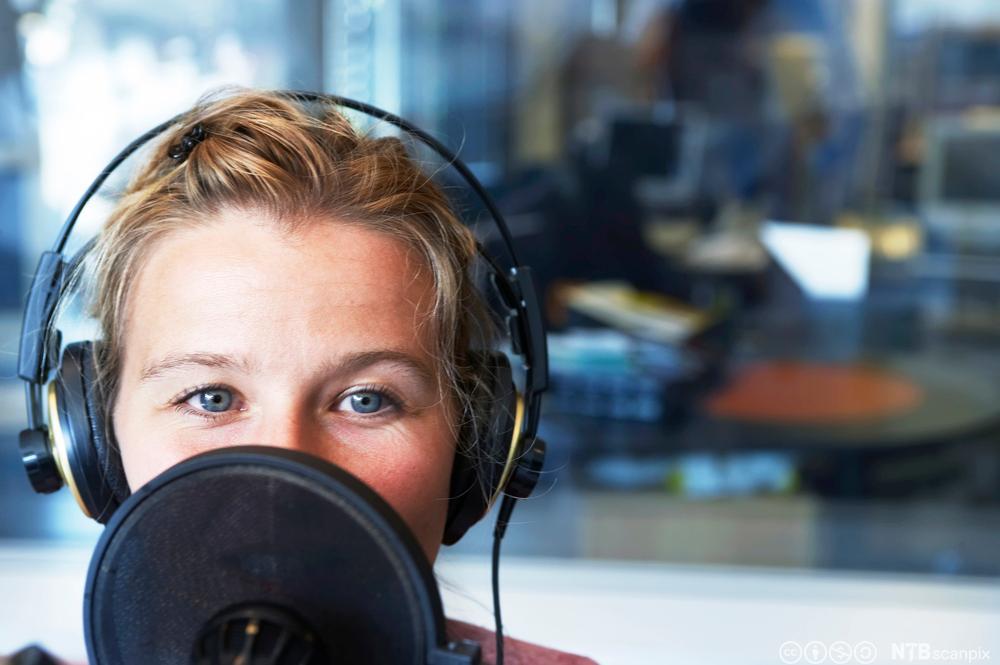 Kvinne som snakker i mikrofon i radiostudio. Foto.