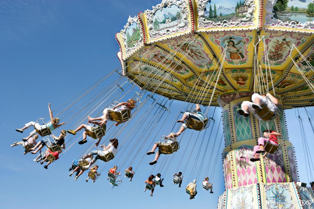Mennesker på tivoli. Karusell sett underfra. Foto.