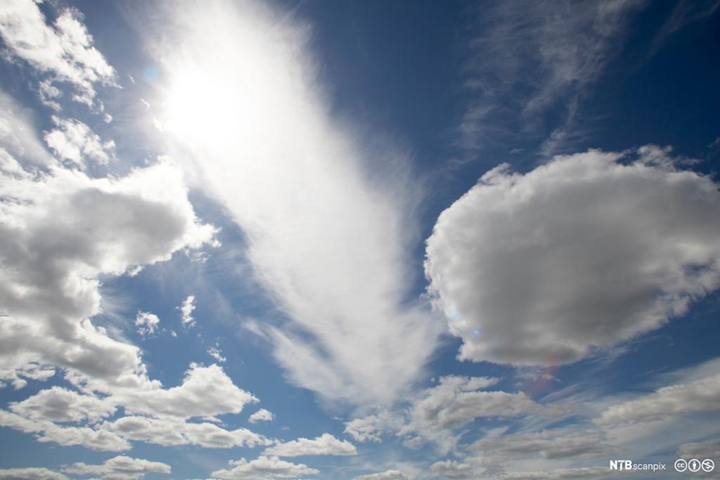 Et fotografi av skyer foran en blå himmel.