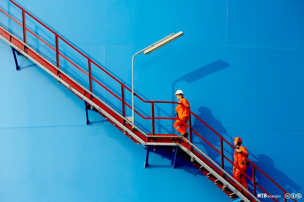 Arbeidere i oransje kjeledresser på vei opp en rød industritrapp. Foto.