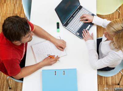 BIlde tatt ovenifra av to unge studenter, en mann og en kvinne som sitter ved et bord med en datamaskin og skriveblokk