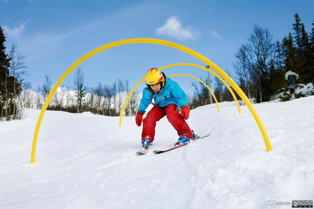 Et barn på ski som kryper gjennom bøyle. Foto.