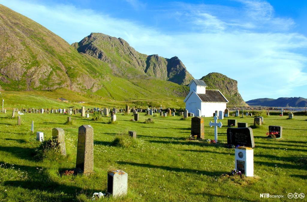 Liten hvit kirke omgitt av gravstøtter. Foto.