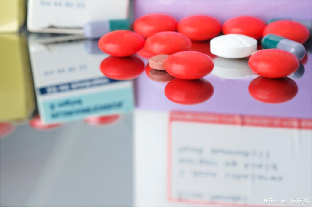 Nærbilde av røde og hvite tabletter. Foto.