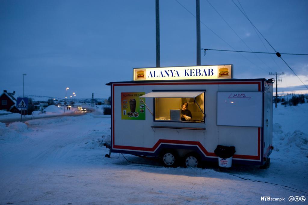Kebab-kiosk plassert i landleg vinterlandskap. Foto.
