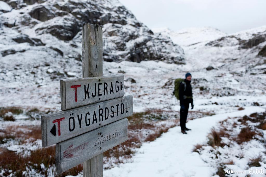 Tursti på fjellet med veiskilt. Foto.
