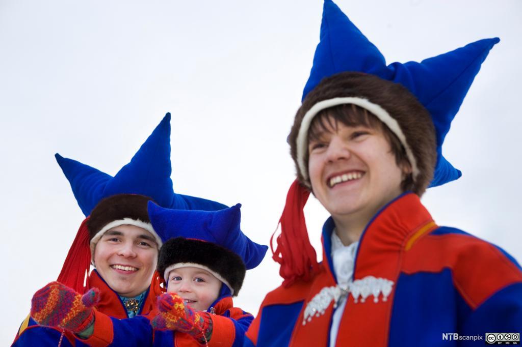 Unge samiske gutter fra Karasjok kledd i kofter med tilhørende hodeplagg. Foto.