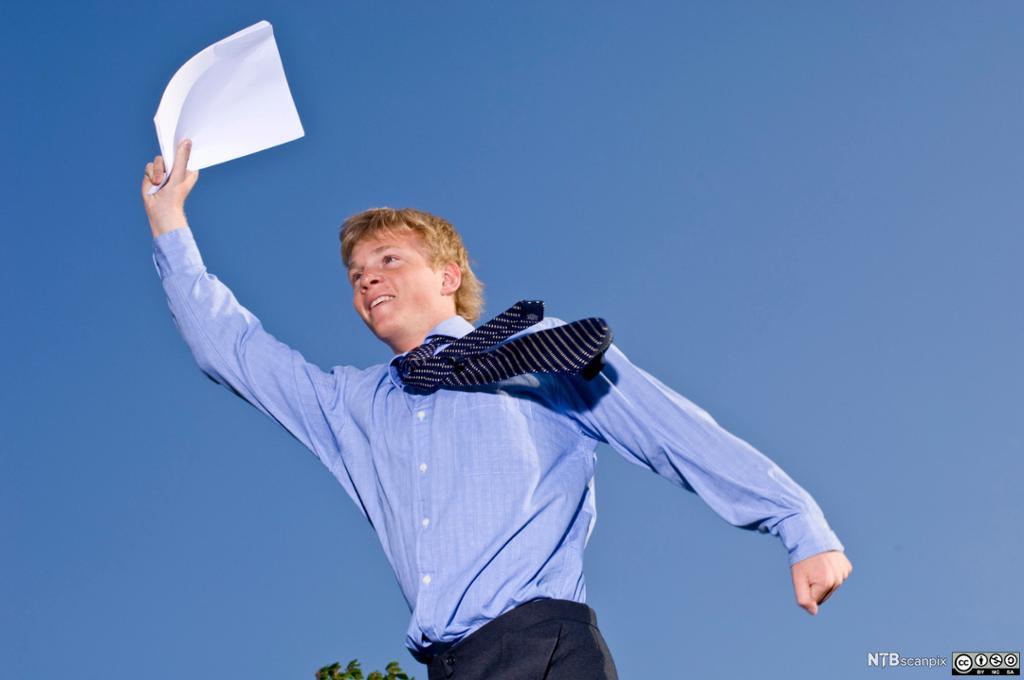 En ung mann med skjorte og slips løper fornøyd med en kontrakt i hånden. Foto.