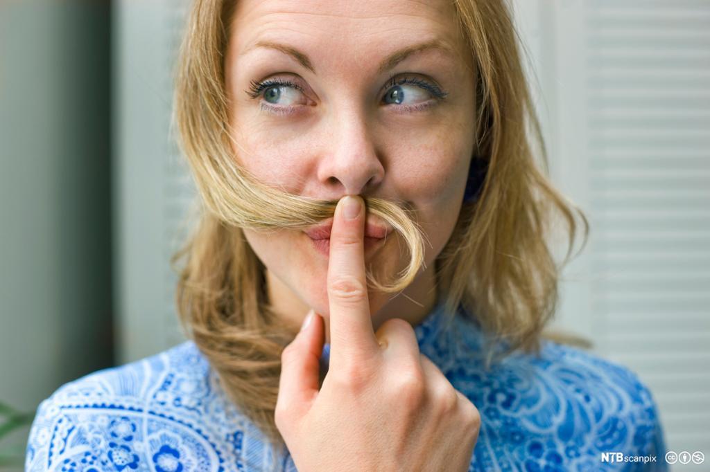 Kvinne som ser tankefull ut og holder en hårlokk under nesa. Foto.