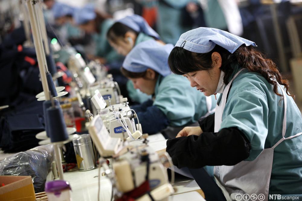 Kinesiske kvinner syr klær på en fabrikk. Foto.