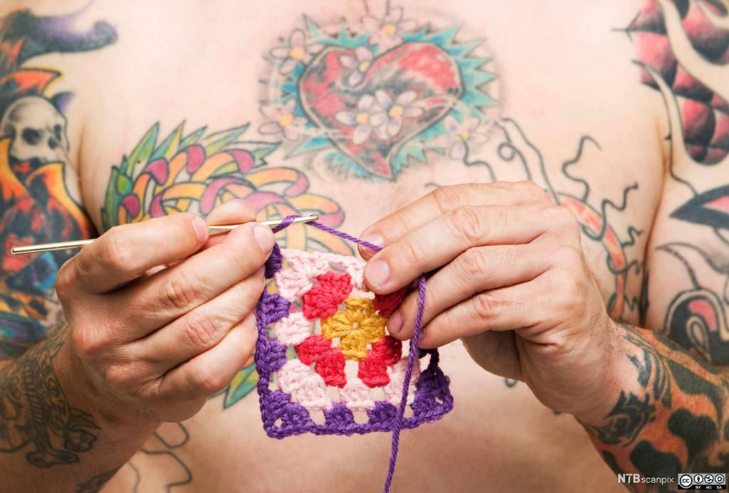 Mannlig tatovert torso hekler en lapp. Foto.