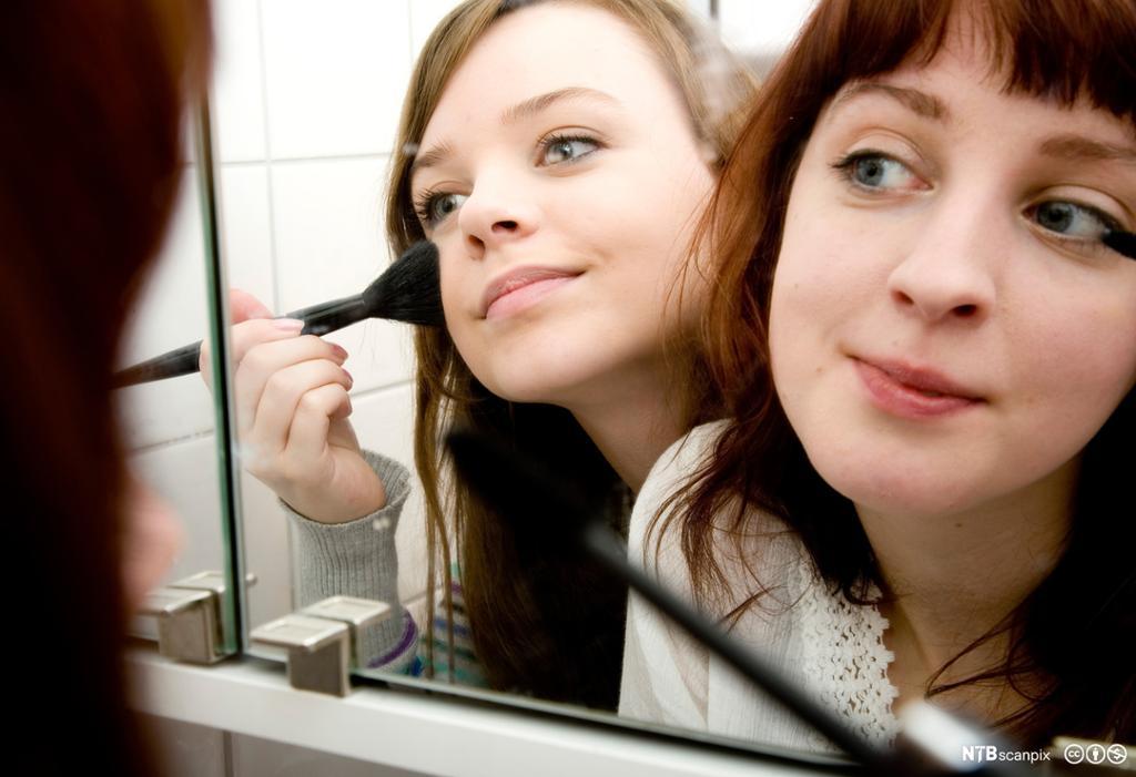 To jenter sminker seg foran speil. Foto.