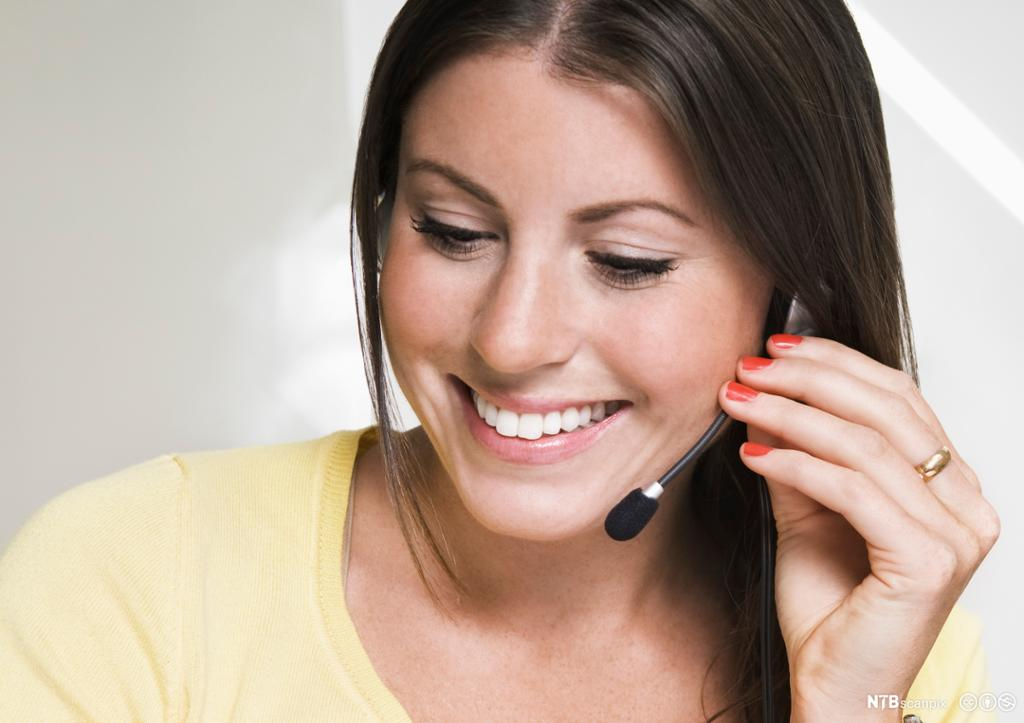 Dame med headset smiler. Foto.