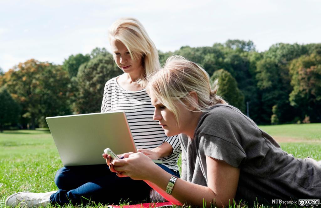 To jenter bruker data i friluft. Foto.