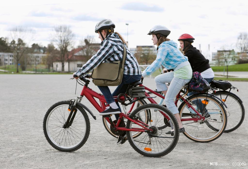 Tre jenter med sykkelhjelm på sykkel. foto.