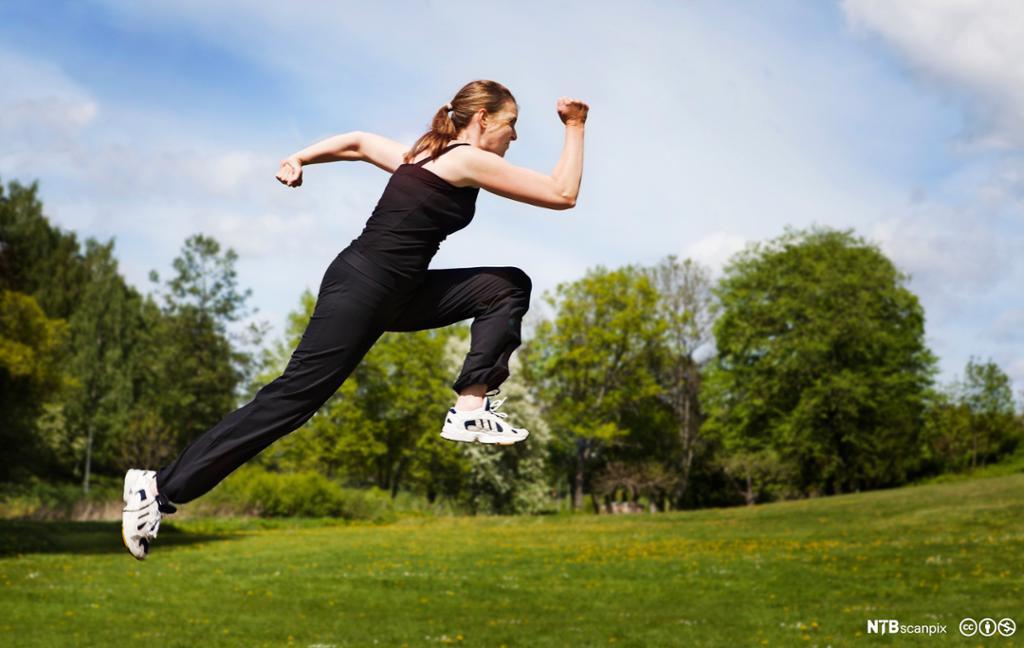 Dame i svarte treningsklær midt i et hopp. Foto.