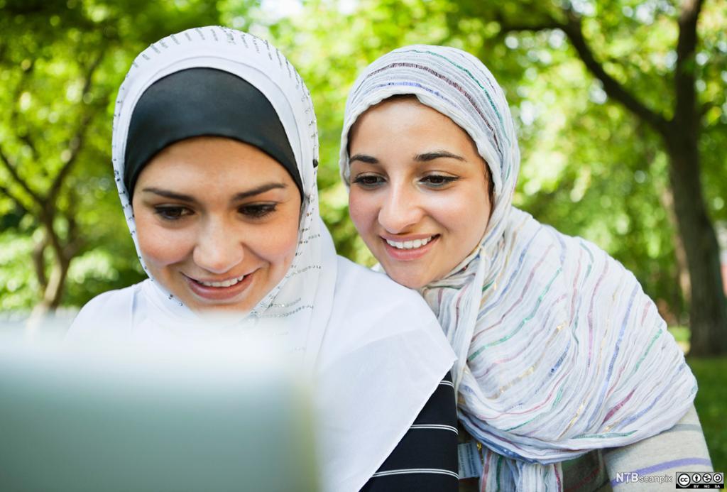 To unge jenter med hidjab ser på PC-skermen. Foto.