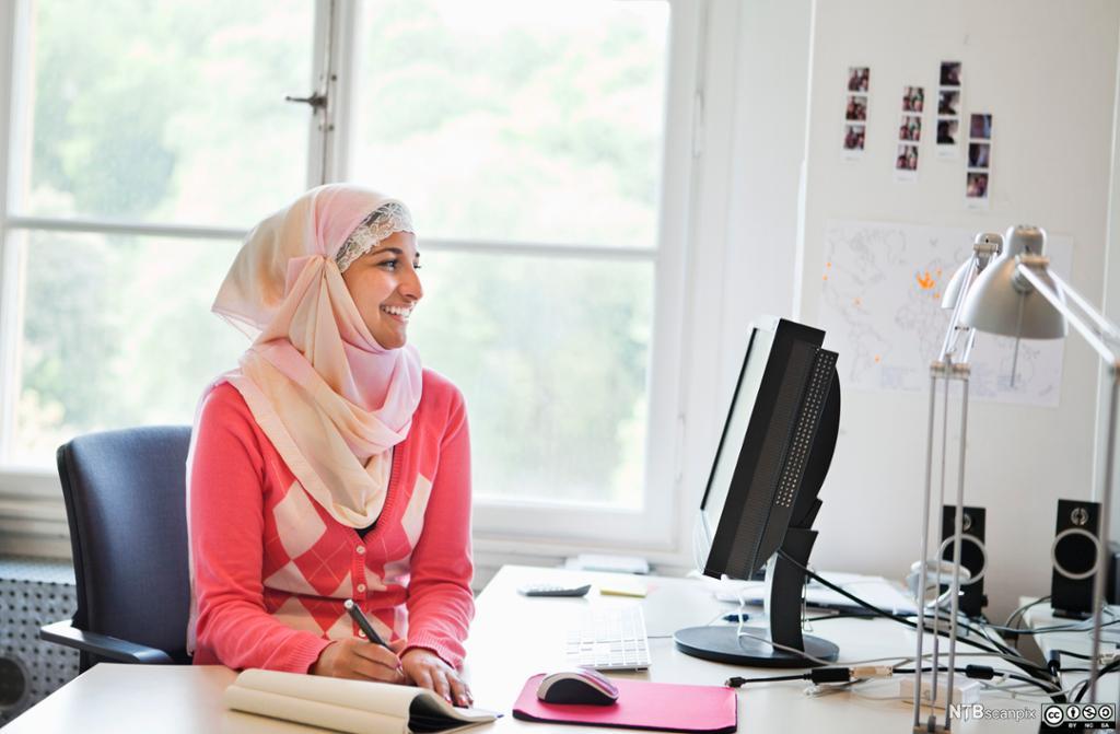 Ung jente i hijab sitter forran en datamaskin og tar notater. Foto.