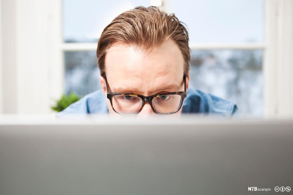 Konsentrert businessmann med briller sitter foran laptopen. Foto.