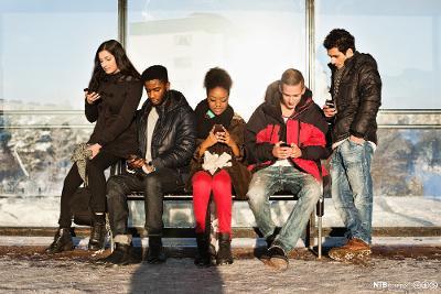 En gjeng med venner med mobiltelefoner på en benk vinterstid. Foto.